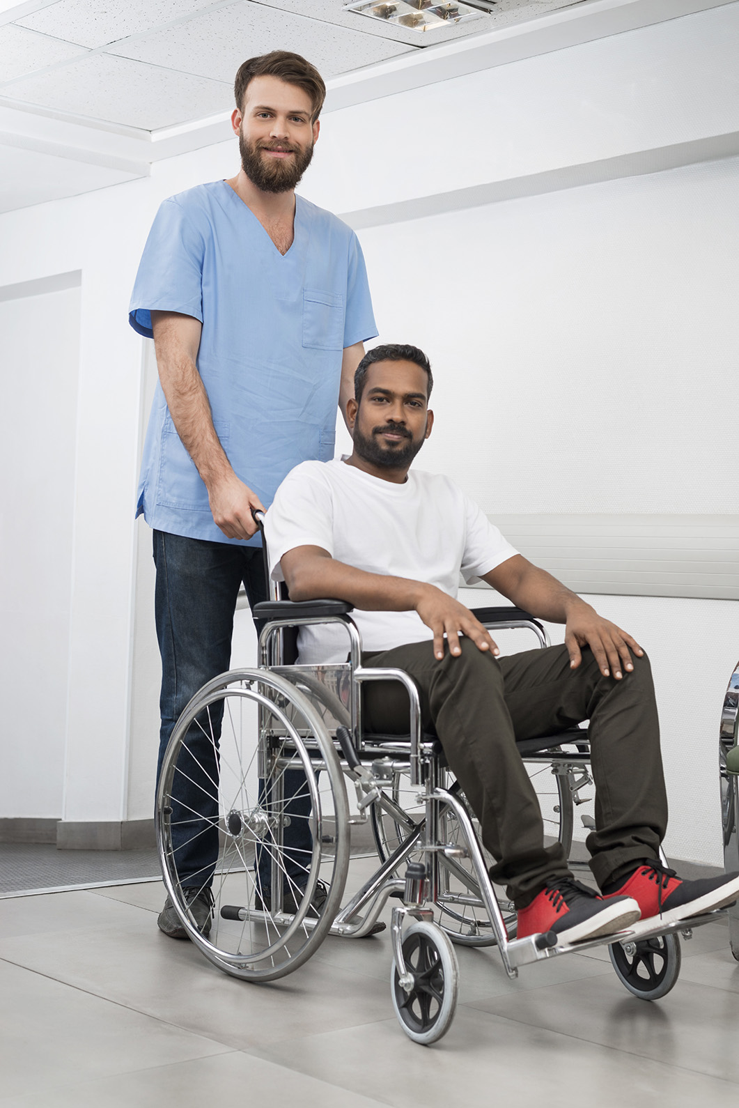 Portrait of smiling male patient sitting in wheelchair while nurse standing behind at hospital