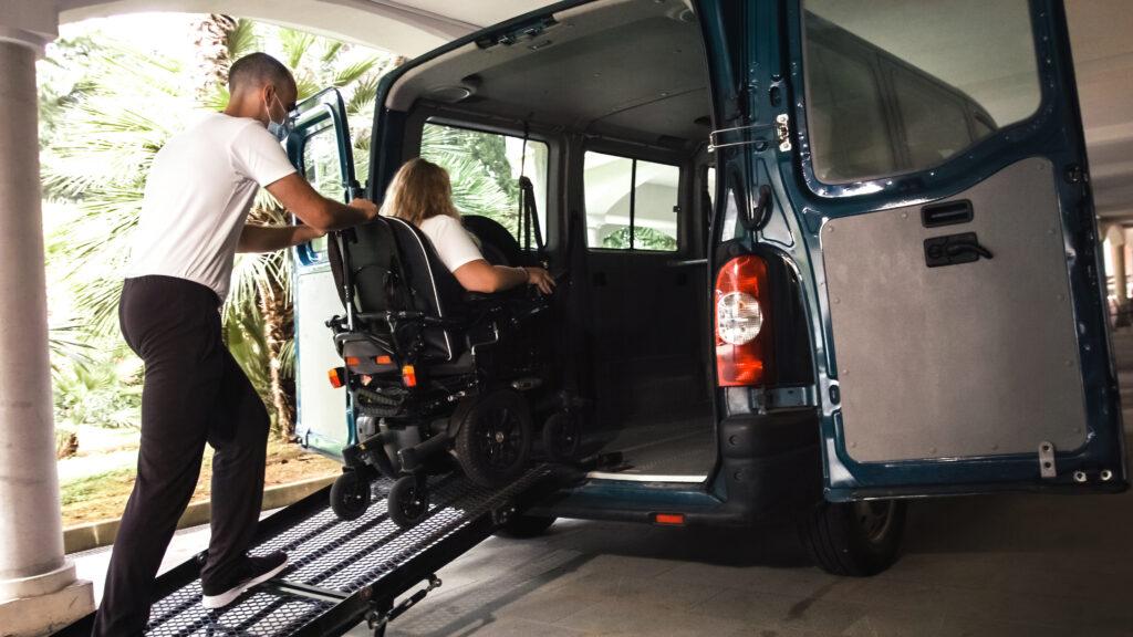 Man pushing woman into wheelchair accessible van.